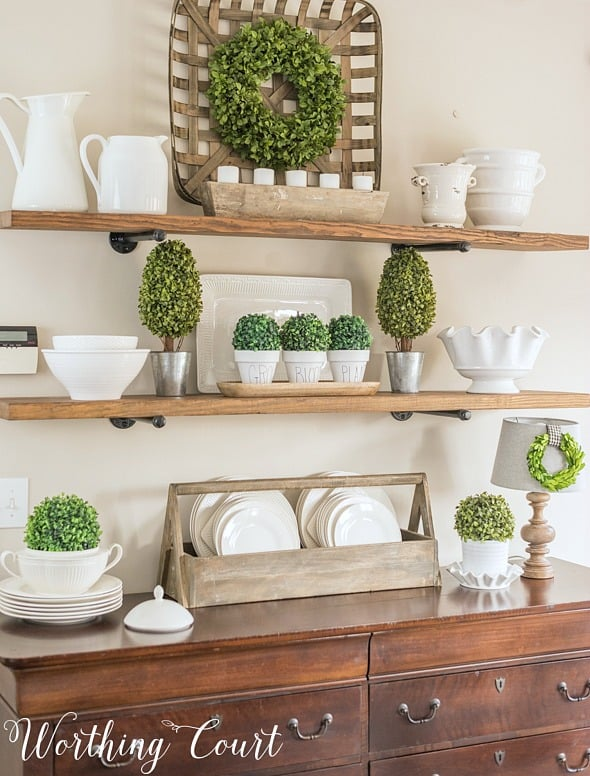 open shelves decorated with white dishes and greenery
