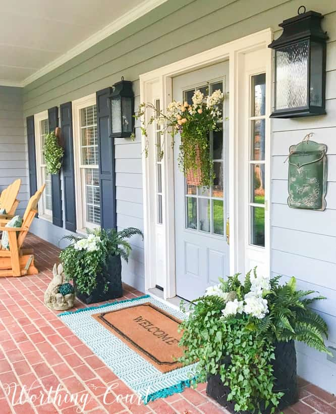 front porch with gray siding and gray front door flanked by planters