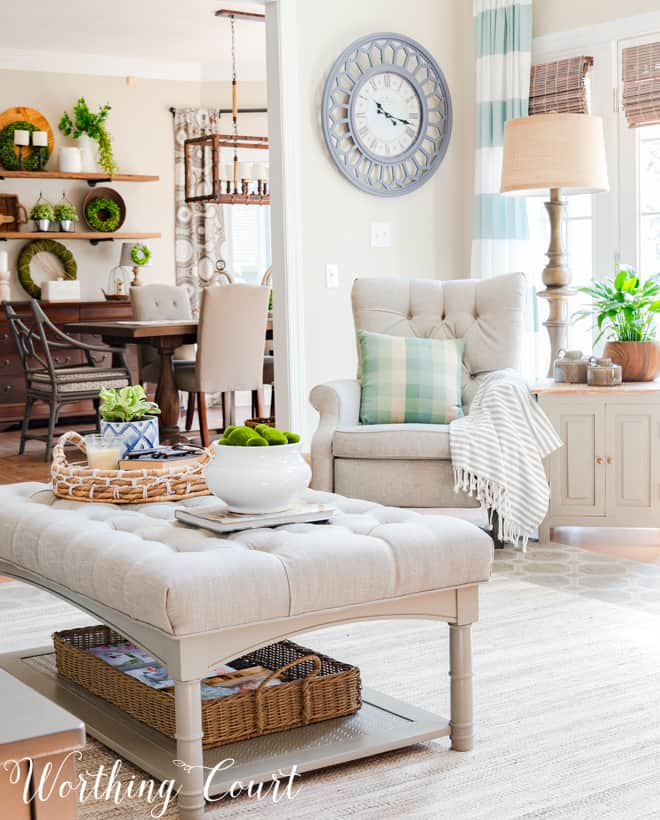 The family room with a large clock on the wall and a neutral ottoman with a tray and a vase on it.