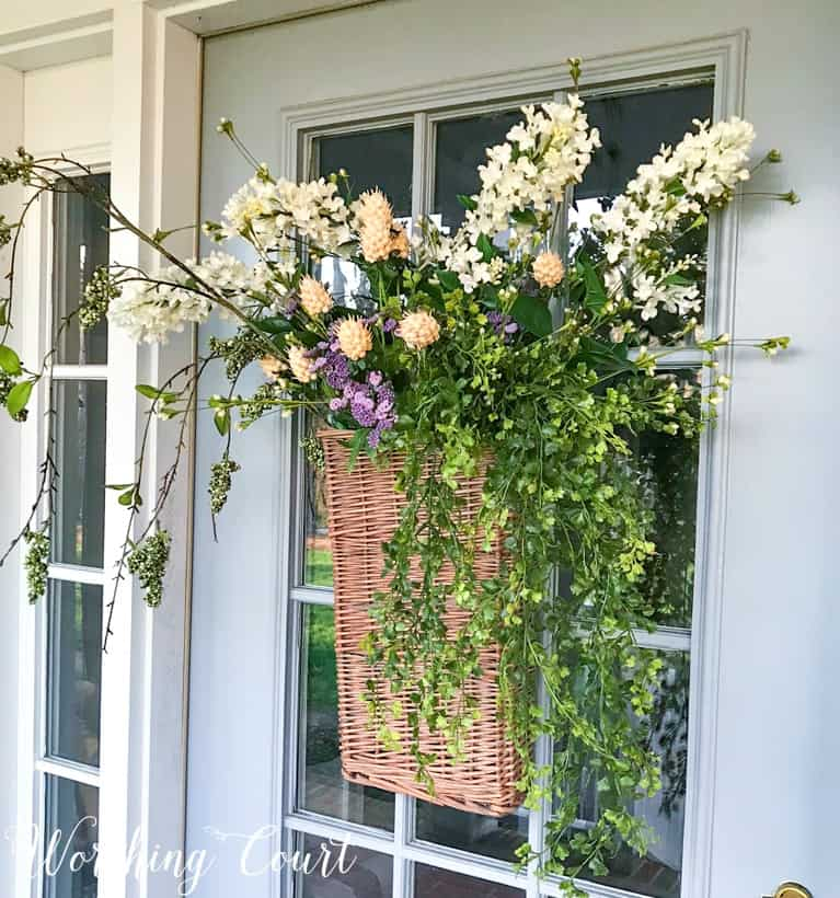 long hanging basket on front door filled with faux greenery stems