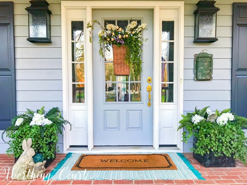 gray front door with sidelights flanked by planters and layered door mats