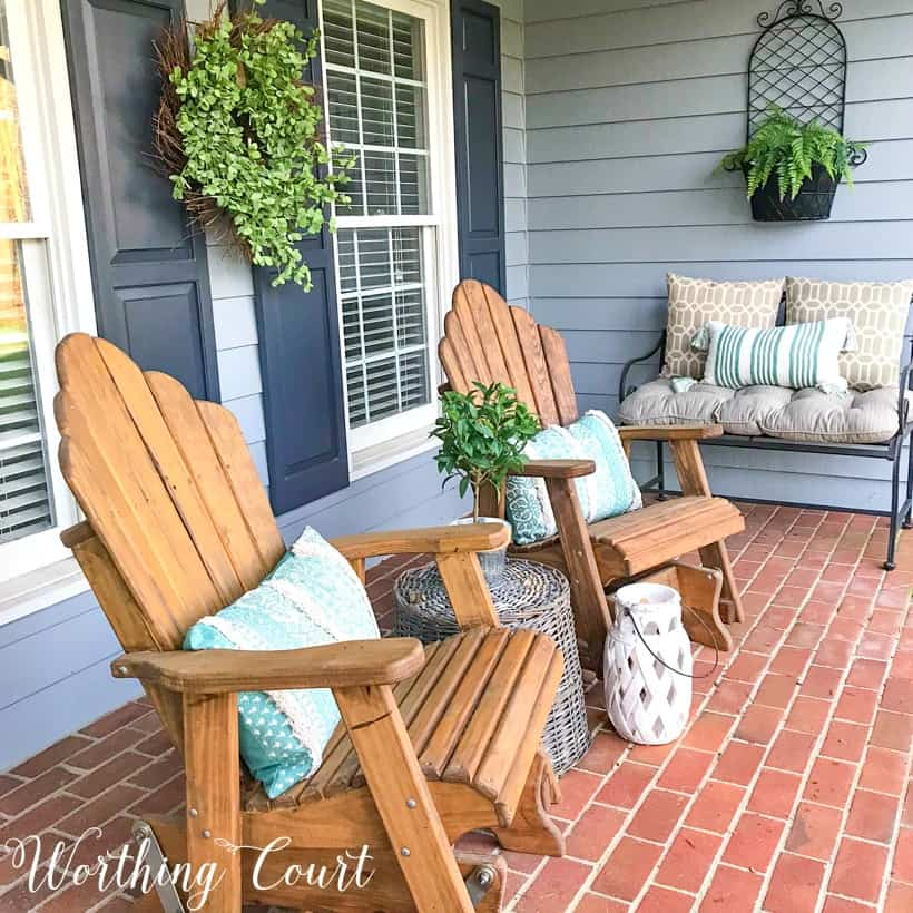 pair of wood stained adirondack chairs on a front porch with gray siding