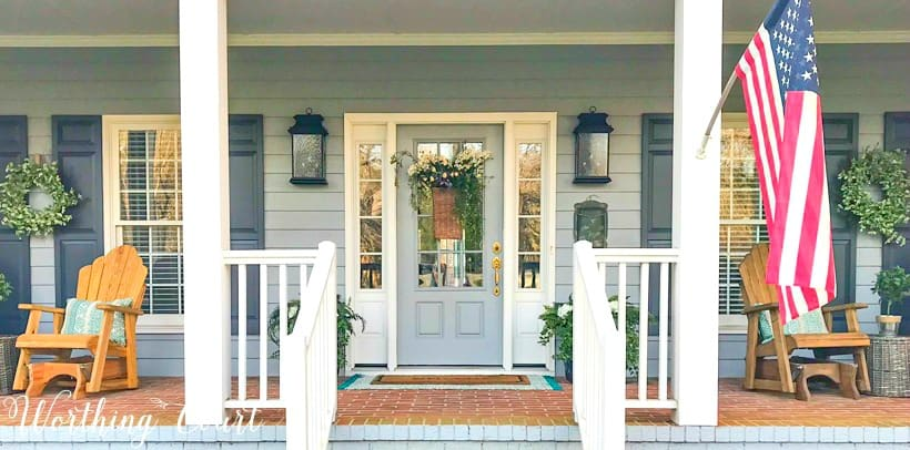front porch with gray siding, white columns and a gray front door with sidelights