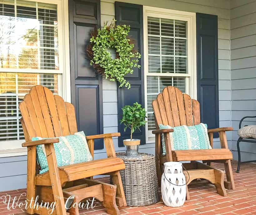 pair of wood stained adirondack chairs on front porch with gray siding
