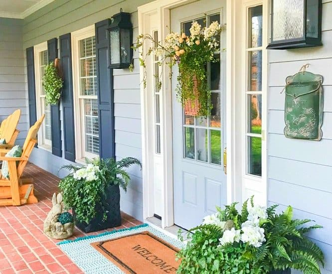 front porch with gray siding and gray front door with sidelights