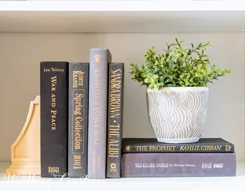 bookshelf vignette with faux greenery and stacked books