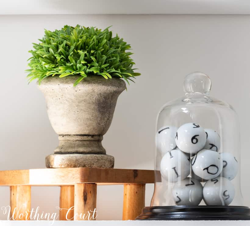 bookcase vignette with faux greenery and a cloche