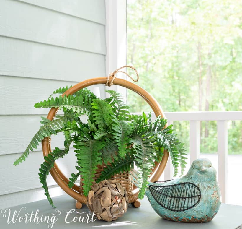 outdoor vignette on a sidetable with bird and fern
