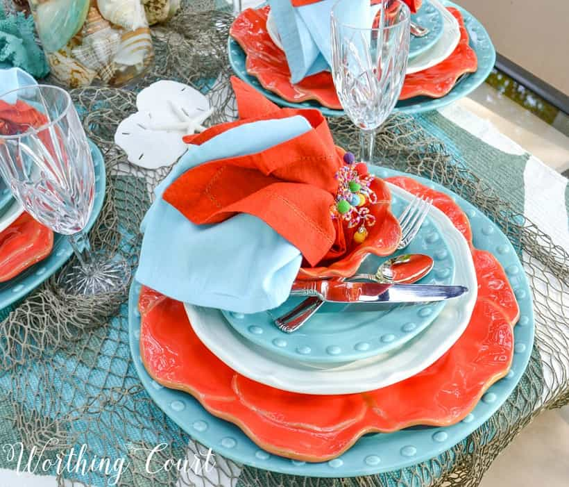 Blue and coral napkins on the plates on the table.
