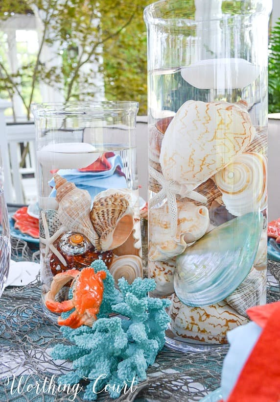 Clear glass cylinders filled with seashells.