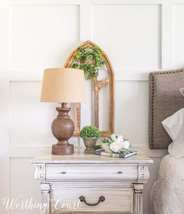 white nightstand with wood lamp and gothic arch art