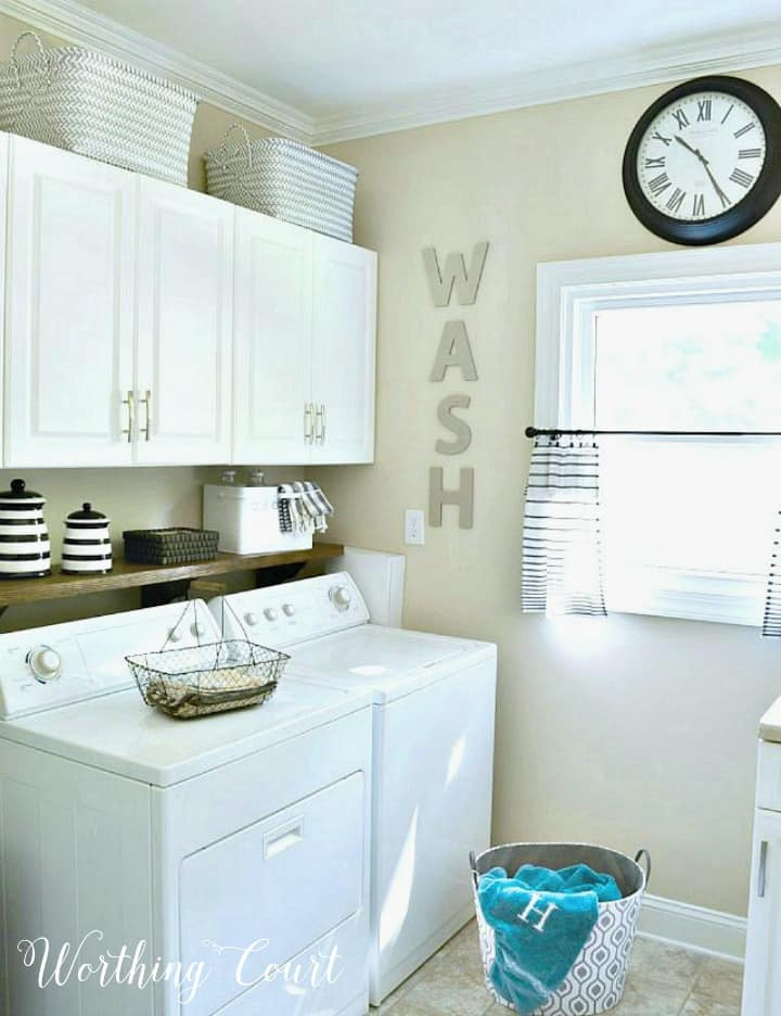 laundry room with white washer and dryer, white cabinets and beige walls