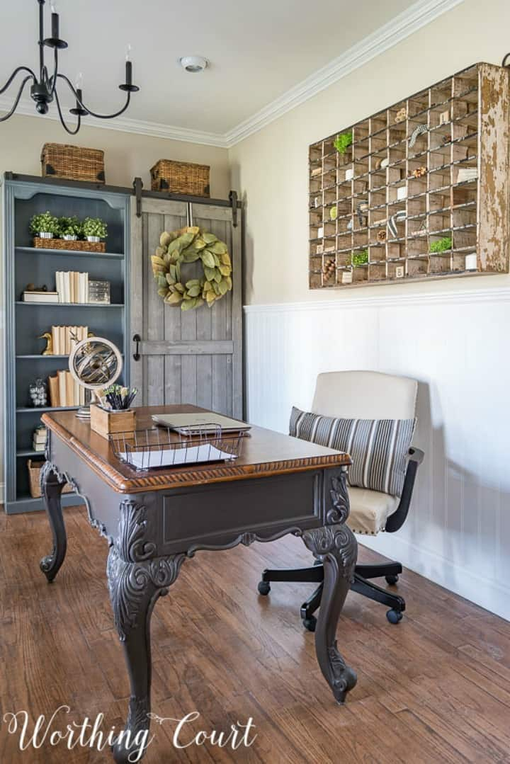 home office with gray bookcase with a sliding door, desk and chair and vintage mail sorter on the wall