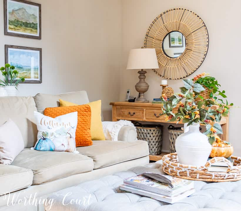 Neutral sofa with fall pillows and a console table with fall decor