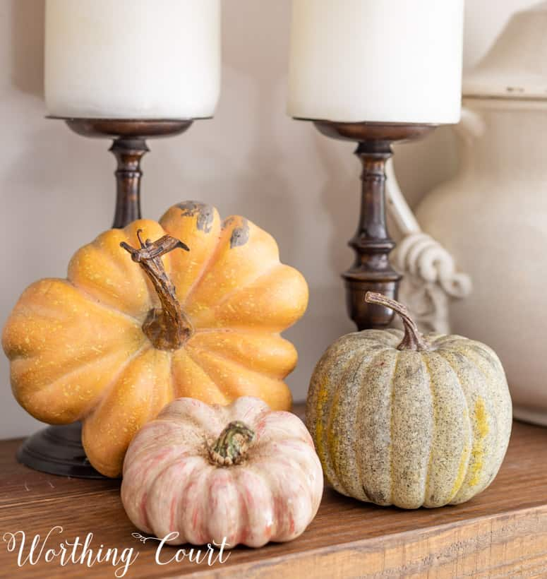 trio of faux pumpkins on a shelf in muted fall colors