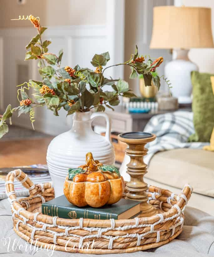 round wicker tray holding fall decorations