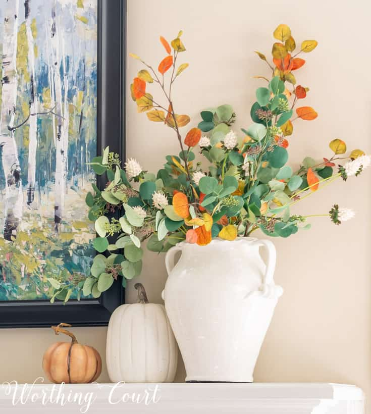 Faux fall eucalyptus stems in a white vase on a fireplace mantel