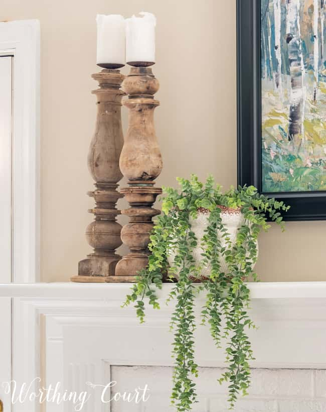 Natural wood candlesticks and trailing greenery on a mantel