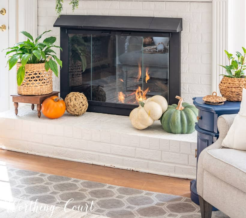 fireplace hearth decorated for fall with faux pumpkins and an indoor plant