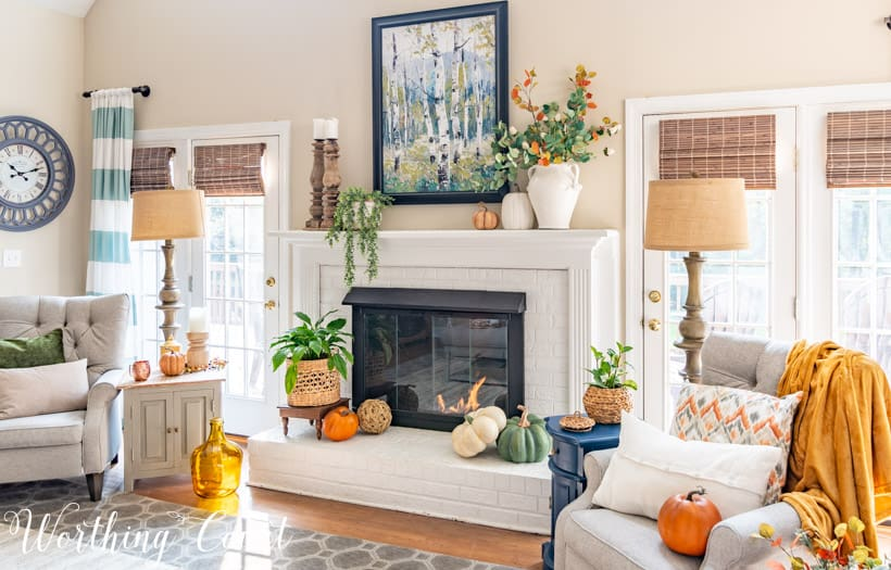 neutral living room and white painted brick fireplace with fall decor