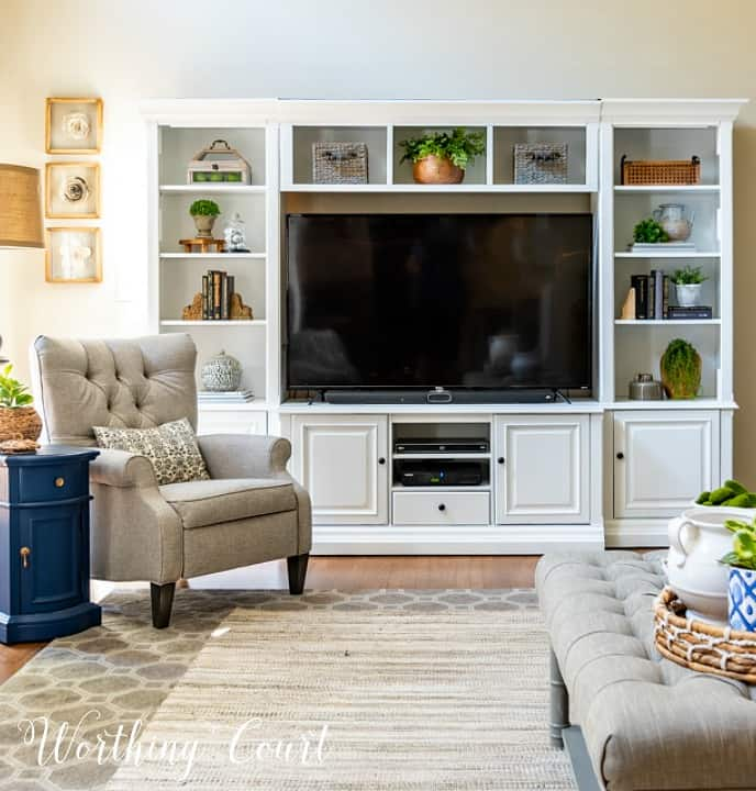 Built in white wall shelving unit with a large TV, decorated shelves.  There is a neutral armchair in the corner of the room.