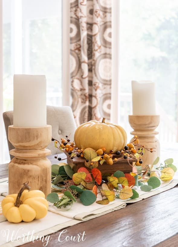 fall centerpiece with chunky wood candlesticks and faux eucalyptus in fall colors