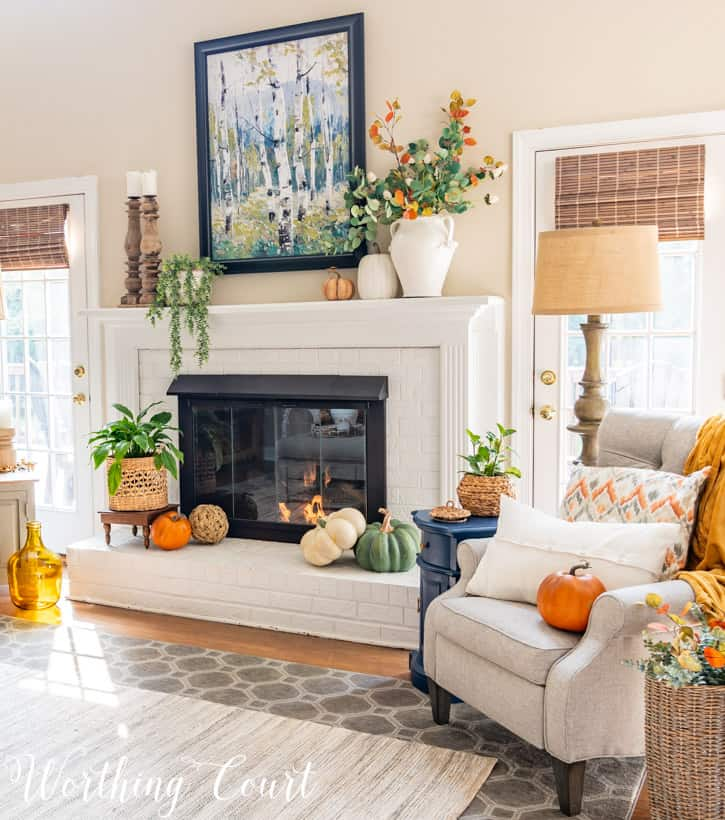 white brick fireplace decorated with traditional fall colors