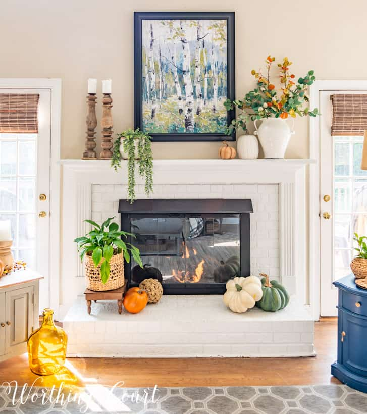 Brick fireplace painted white with fall decor in traditional colors