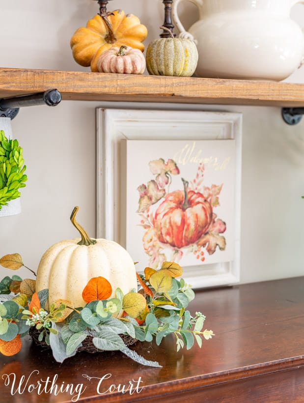 fall vignette with a faux pumpkin nestled in a ring of greenery