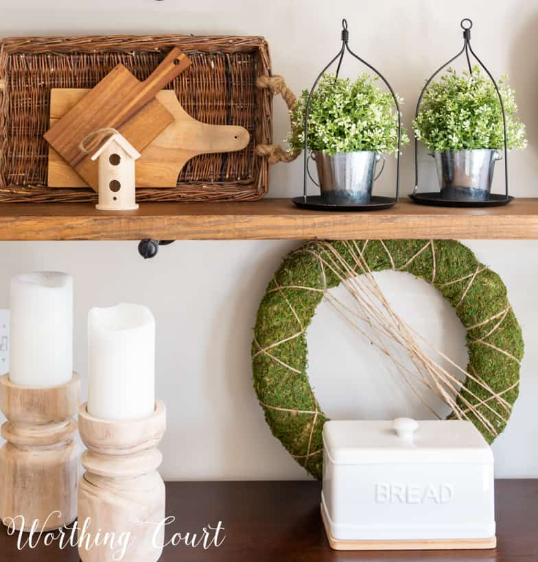 Showing how to layer decor items on the open shelves.