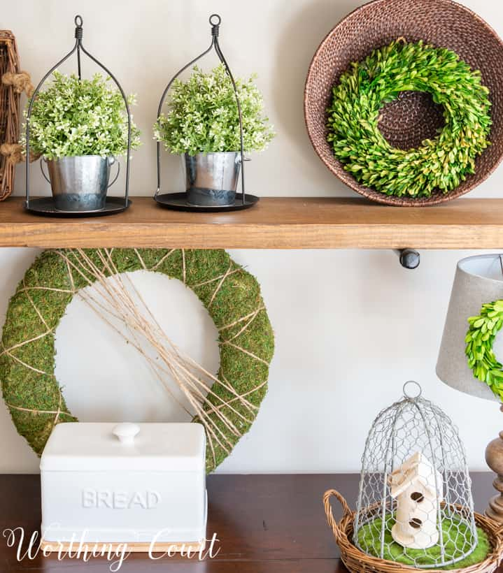 Green wreaths are on the shelf, as well as silver pewter decor items.
