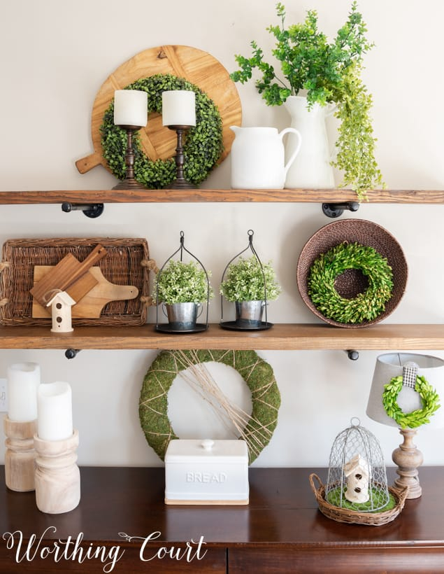 The various texture of decor items on the shelf, such as the greenery, plus porcelain, and wicker baskets on the shelf.