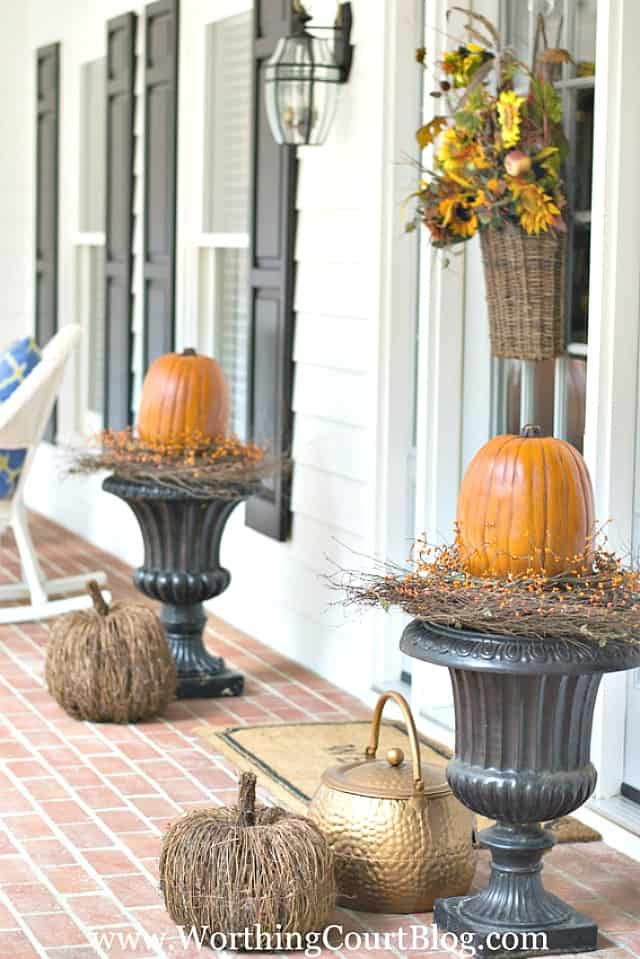 black urns topped with large pumpkins for fall