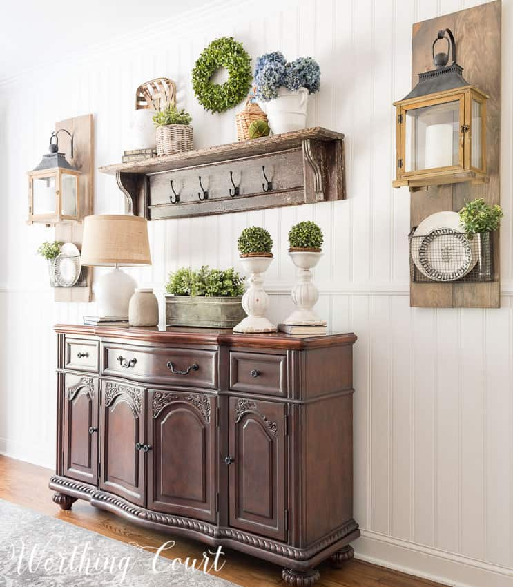 A single wooden shelf with hooks and on top decorated with a wicker basket and white porcelain filled with hydrangeas.