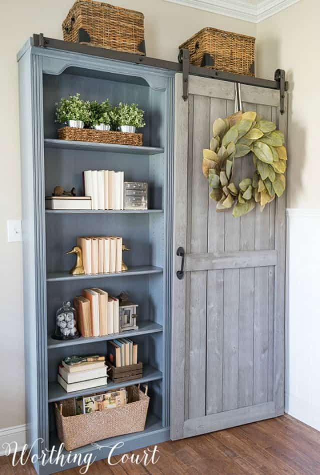 A wooden blue slate grey bookcase in the office. It has a barn door style sliding door.