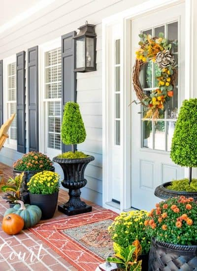 front porch decorate for fall with mums and pumpkins