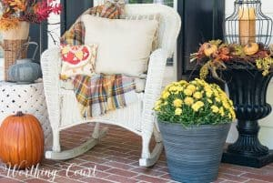 white wicker rocking chair with fall pillows