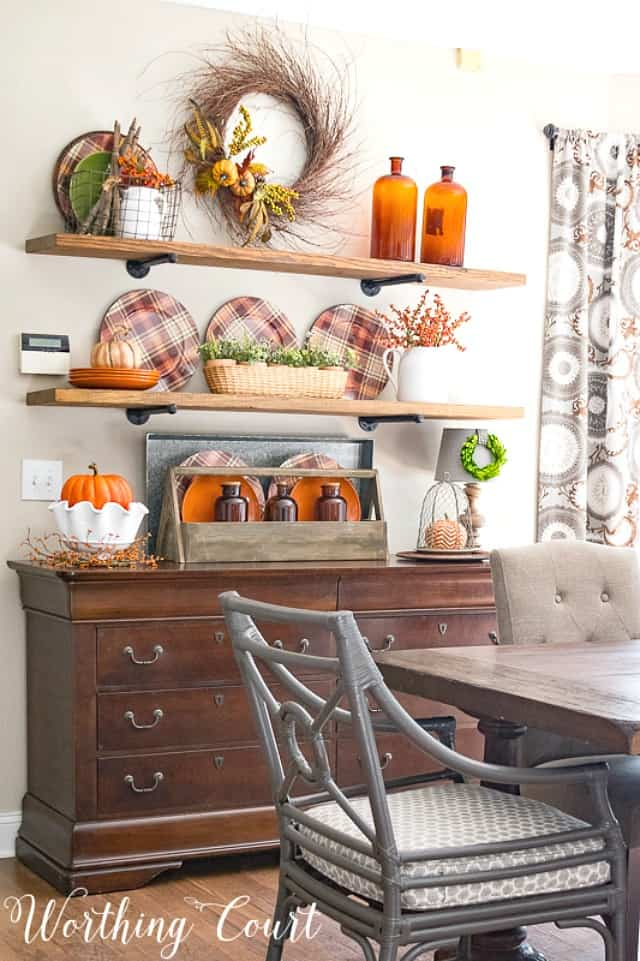 Open floating shelves decorated for fall with amber glass, plaid plates and a fall wreath.
