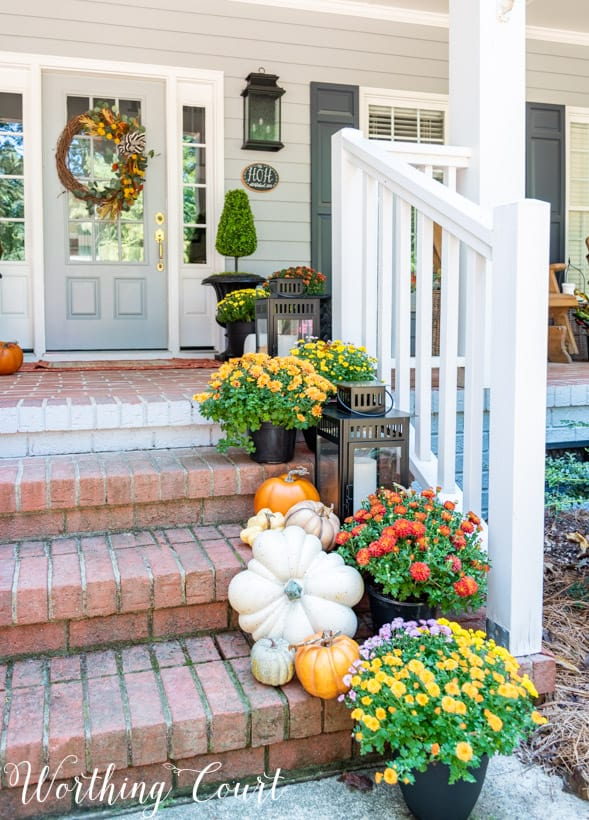 front porch decor ideas showing mums trailing up porch steps