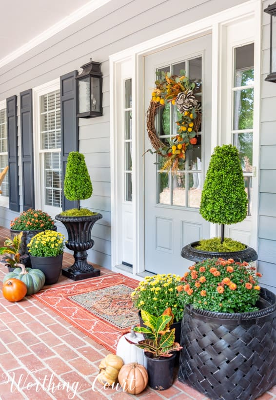front porch decor ideas for fall with mums, pumpkins and a fall wreath