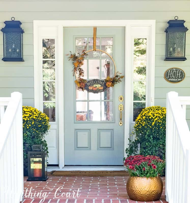front porch decorated for fall with mums