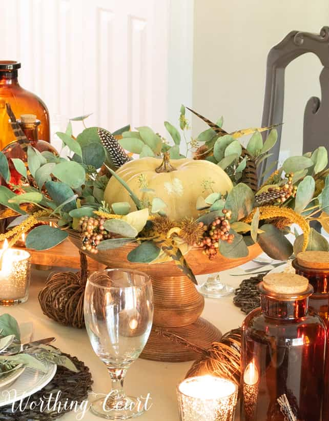 There is a large pumpkin centerpiece with greenery and feathers.