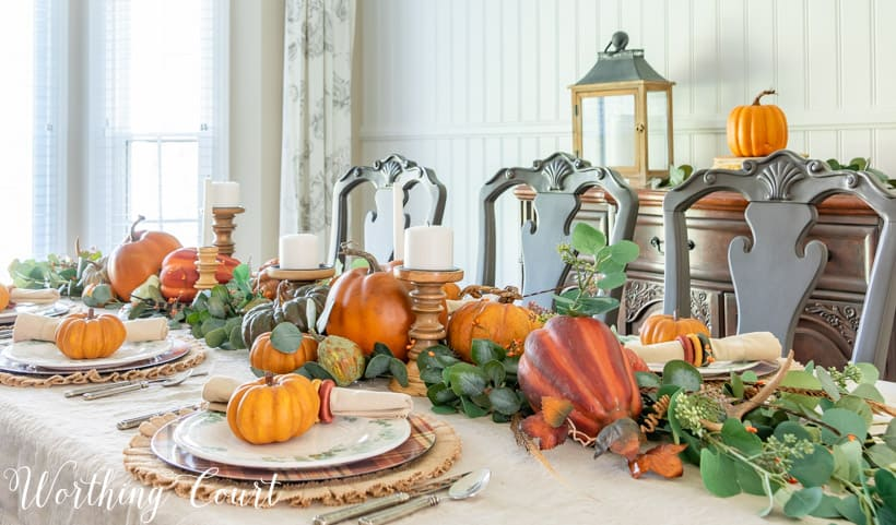 thanksgiving table set with orange pumpkins and eucalyptus on a linen tablecloth