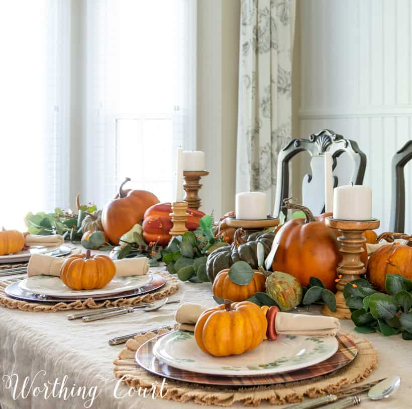 table set for Thanksgiving with pumpkins and eucalyptus