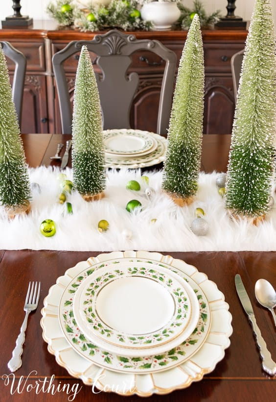 Christmas place setting with ivory plates with holly leaves and a gold rim