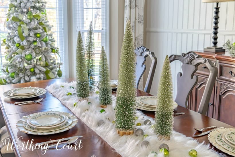 dining room table set for Christmas with green, silver and gold