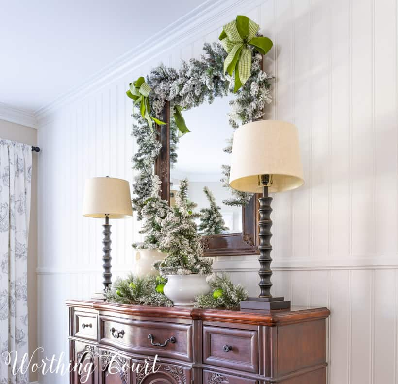 sideboard decorated for Christmas with flocked trees and garland