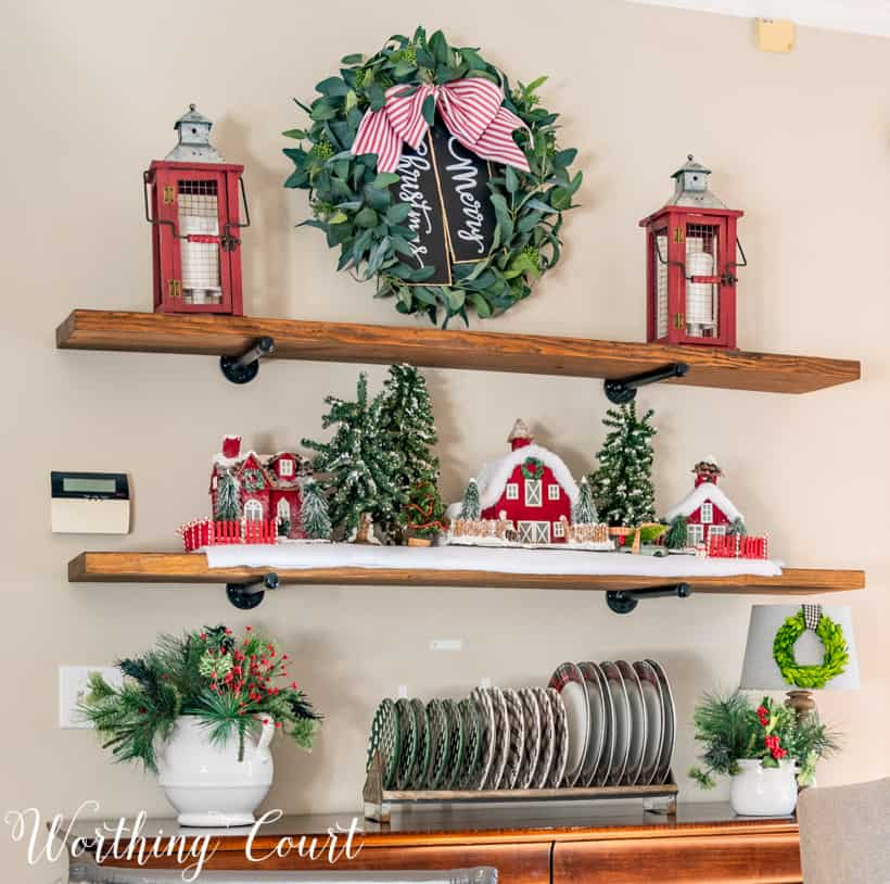 A eucalyptus wreath with a red and white bow on the wooden shelving unit.
