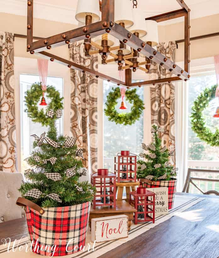 Christmas centerpiece with mini trees in plaid containers and red lanterns.