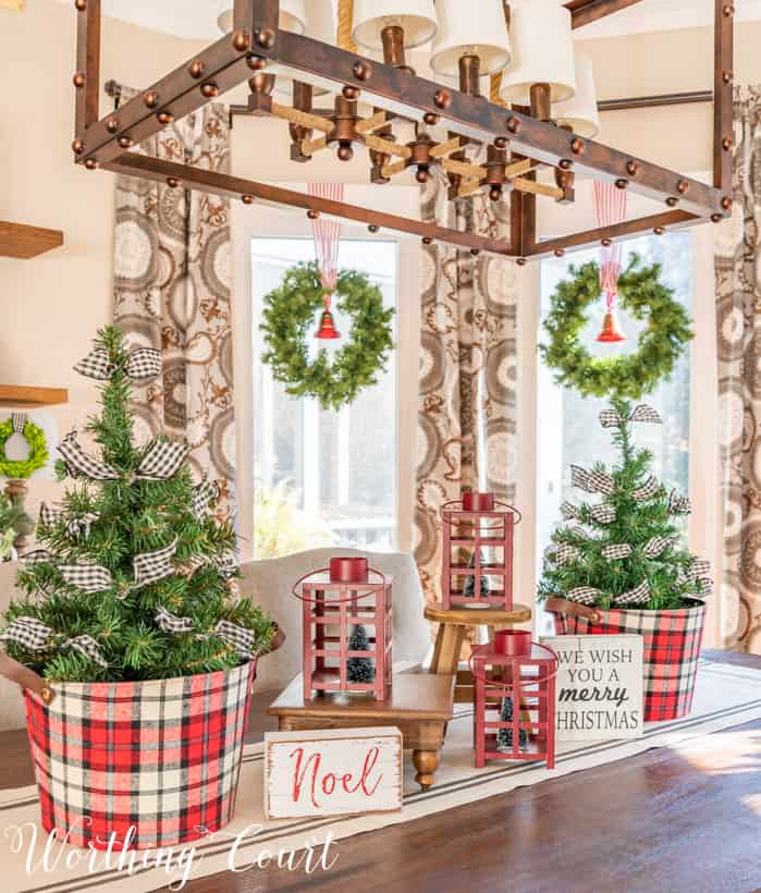 Christmas centerpiece with min trees in plaid containers and red lanterns